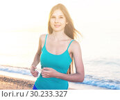 Купить «Smiling adult woman in blue T-shirt is jogging», фото № 30233327, снято 4 августа 2017 г. (c) Яков Филимонов / Фотобанк Лори
