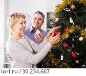 Купить «Woman and man are hang up New Year's toys on a fir-tree», фото № 30234667, снято 19 марта 2019 г. (c) Яков Филимонов / Фотобанк Лори