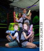 Купить «Kids sitting back to back with laser guns», фото № 30234739, снято 6 июня 2018 г. (c) Яков Филимонов / Фотобанк Лори