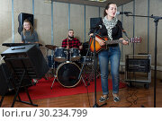 Купить «excited girl rock singer with guitar during rehearsal», фото № 30234799, снято 26 октября 2018 г. (c) Яков Филимонов / Фотобанк Лори