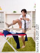 Купить «Young man ironing in the bedroom», фото № 30237227, снято 29 ноября 2018 г. (c) Elnur / Фотобанк Лори
