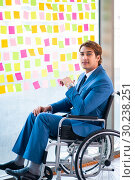 Купить «Young handsome man in wheelchair with many conflicting prioritie», фото № 30238251, снято 25 августа 2018 г. (c) Elnur / Фотобанк Лори