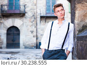 Купить «young European guy in shirt and trousers with suspenders walking around city», фото № 30238555, снято 27 июня 2018 г. (c) Татьяна Яцевич / Фотобанк Лори