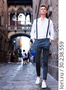 Купить «young European guy in shirt and trousers with suspenders walking around city», фото № 30238559, снято 27 июня 2018 г. (c) Татьяна Яцевич / Фотобанк Лори
