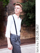 Купить «young European guy in shirt and trousers with suspenders walking around city», фото № 30238567, снято 27 июня 2018 г. (c) Татьяна Яцевич / Фотобанк Лори