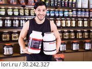 Young bodybuilder showing power and holding pot of sport nutrition products in shop. Стоковое фото, фотограф Яков Филимонов / Фотобанк Лори