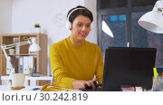 Купить «creative woman in headphones with laptop at office», видеоролик № 30242819, снято 28 февраля 2019 г. (c) Syda Productions / Фотобанк Лори