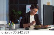 Купить «businesswoman eating and working at night office», видеоролик № 30242859, снято 28 февраля 2019 г. (c) Syda Productions / Фотобанк Лори