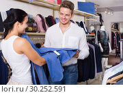 Купить «Young customers selecting jacket», фото № 30252591, снято 24 октября 2016 г. (c) Яков Филимонов / Фотобанк Лори