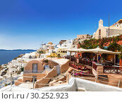 View on Oia town with a cafe on the foreground. Santorini, Greece (2017 год). Редакционное фото, фотограф Наталья Волкова / Фотобанк Лори