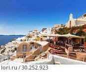 Купить «View on Oia town with a cafe on the foreground. Santorini, Greece», фото № 30252923, снято 8 июня 2017 г. (c) Наталья Волкова / Фотобанк Лори