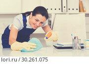 Купить «Portrait of adult female cleaning office table», фото № 30261075, снято 2 июня 2017 г. (c) Яков Филимонов / Фотобанк Лори