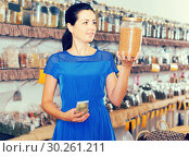 Купить «adult female choosing natural dried herbs sold by weight in eco shop», фото № 30261211, снято 13 июня 2017 г. (c) Яков Филимонов / Фотобанк Лори
