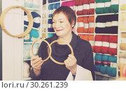 Купить «Woman choosing embroidery hoops for fancywork», фото № 30261239, снято 10 мая 2017 г. (c) Яков Филимонов / Фотобанк Лори