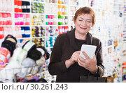 Купить «Woman with shopping bags using phone», фото № 30261243, снято 10 мая 2017 г. (c) Яков Филимонов / Фотобанк Лори
