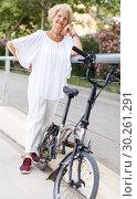 Купить «Senior woman resting near bike», фото № 30261291, снято 6 июля 2018 г. (c) Яков Филимонов / Фотобанк Лори