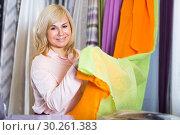 Купить «Mature woman customer choosing color curtains», фото № 30261383, снято 17 января 2018 г. (c) Яков Филимонов / Фотобанк Лори