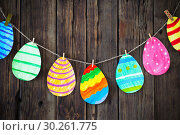 Купить «Paper Easter painted eggs painted hang on clothespins on background old wooden wall.», фото № 30261775, снято 6 марта 2019 г. (c) Майя Крученкова / Фотобанк Лори
