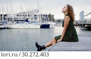 Купить «Young attractive woman tourist sitting at quay with sailboats on background in Barcelona», видеоролик № 30272403, снято 27 октября 2018 г. (c) Яков Филимонов / Фотобанк Лори