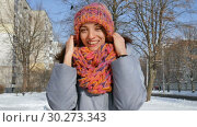 Beautiful adult girl in warm coat and colorful knitted hat and scarf having fun outdoors during sunny day in spring on blue sky background. Стоковое видео, видеограф Ольга Балынская / Фотобанк Лори