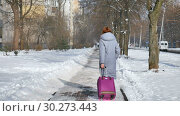 Back view of young adult girl in warm coat and colorful knitted scaft walking pulling her big violet suitcase during early spring time on blue sky background outdoors. Стоковое видео, видеограф Ольга Балынская / Фотобанк Лори