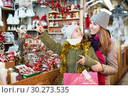 Купить «Girl with woman choosing Christmas gifts for family», фото № 30273535, снято 19 декабря 2017 г. (c) Яков Филимонов / Фотобанк Лори