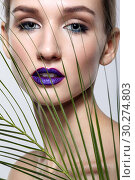 Купить «Female portrait with palm branch leaves on foreground and beauty face makeup with violet lips.», фото № 30274803, снято 4 марта 2019 г. (c) Serg Zastavkin / Фотобанк Лори
