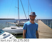 Portrait of a young man standing on the pier on the background of the sea with yachts. Стоковое фото, фотограф Дмитрий Морозов / Фотобанк Лори