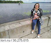 Portrait of a middle-aged woman on the waterfront on the background of a river with a pleasure boat. Стоковое фото, фотограф Дмитрий Морозов / Фотобанк Лори