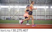 Купить «Two young athletic women running in covered area», видеоролик № 30275407, снято 21 марта 2019 г. (c) Константин Шишкин / Фотобанк Лори