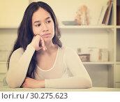 Купить «Gloomy girl sitting at the table», фото № 30275623, снято 30 мая 2017 г. (c) Яков Филимонов / Фотобанк Лори