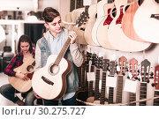Купить «teenage customers deciding on suitable acoustic guitar in guitar shop», фото № 30275727, снято 14 февраля 2017 г. (c) Яков Филимонов / Фотобанк Лори