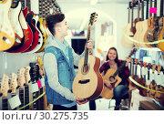 Купить «teenage customers deciding on suitable acoustic guitar in guitar shop», фото № 30275735, снято 14 февраля 2017 г. (c) Яков Филимонов / Фотобанк Лори