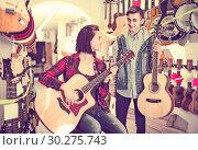Купить «teenage customers deciding on suitable acoustic guitar in guitar shop», фото № 30275743, снято 14 февраля 2017 г. (c) Яков Филимонов / Фотобанк Лори