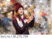 Купить «Beautiful young girl choosing Christmas decoration», фото № 30275799, снято 22 декабря 2016 г. (c) Яков Филимонов / Фотобанк Лори