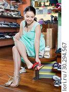 Купить «Girl is trying on heeled sandals in shoes shop», фото № 30294567, снято 10 мая 2017 г. (c) Яков Филимонов / Фотобанк Лори