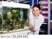 Купить «Girl looking at striped tropical fish in aquarium with rocks and seaweed inside», фото № 30294643, снято 17 февраля 2017 г. (c) Яков Филимонов / Фотобанк Лори