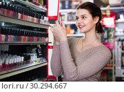 Купить «Smiling woman customer browsing rows of lipstick», фото № 30294667, снято 21 февраля 2017 г. (c) Яков Филимонов / Фотобанк Лори