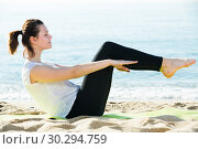 Купить «Adult female in white T-shirt is practicing yoga», фото № 30294759, снято 15 мая 2017 г. (c) Яков Филимонов / Фотобанк Лори