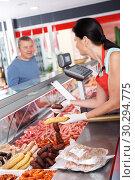 Купить «Young seller helping male choosing sausages», фото № 30294775, снято 22 июня 2018 г. (c) Яков Филимонов / Фотобанк Лори