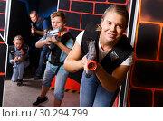 Купить «Emotional girl with laser pistol playing laser tag with friends», фото № 30294799, снято 3 сентября 2018 г. (c) Яков Филимонов / Фотобанк Лори