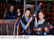 Купить «Happy teen brother and sister standing with laser pistols during laser tag game with parents in labyrinth», фото № 30294823, снято 3 сентября 2018 г. (c) Яков Филимонов / Фотобанк Лори