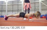 Купить «Young fit athletic woman in sports clothes doing push ups.», видеоролик № 30295131, снято 21 марта 2019 г. (c) Константин Шишкин / Фотобанк Лори