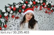 Купить «Joyful happy girl in red santa hat send a kiss looking at the camera in Christmas decorated studio», видеоролик № 30295403, снято 3 декабря 2018 г. (c) Ольга Балынская / Фотобанк Лори