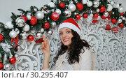 Купить «Beautiful young woman with dark curly hair is touching white and red christmas balls in decorated studio and smiling», видеоролик № 30295407, снято 3 декабря 2018 г. (c) Ольга Балынская / Фотобанк Лори