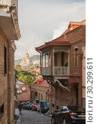 Купить «Scenic view of old city Tbilisi, narrow steep street coming down from hill overlooking the Cathedral of Holy Trinity», фото № 30299611, снято 23 сентября 2018 г. (c) Юлия Бабкина / Фотобанк Лори