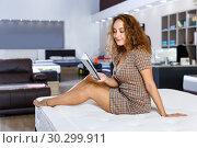 Купить «Young attractive woman choosing right mattress with booklet in home furnishings store», фото № 30299911, снято 22 октября 2018 г. (c) Яков Филимонов / Фотобанк Лори