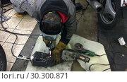 Купить «Сварщик режет выхлопную трубу мотоцикла сварочным аппаратом в огнестойких перчатках. Гараж для ремонта мотоциклов», видеоролик № 30300871, снято 12 марта 2019 г. (c) Кекяляйнен Андрей / Фотобанк Лори