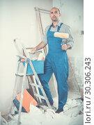 Repairer is standing with roller in uniform. Стоковое фото, фотограф Яков Филимонов / Фотобанк Лори