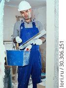 Купить «Man is standing with bucket and putty knife», фото № 30306251, снято 18 мая 2017 г. (c) Яков Филимонов / Фотобанк Лори